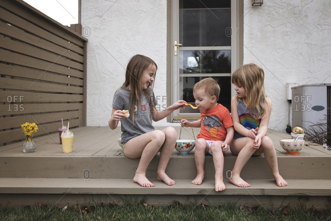 Girl feeding her young brother with spoon on porch