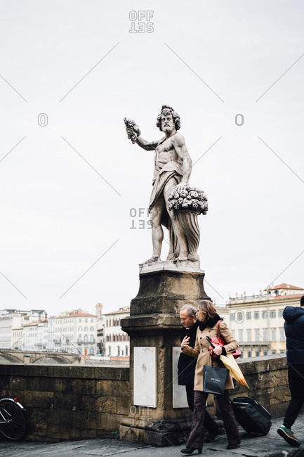 Florence, Italy - February 4, 2017: People walking by bridge statue