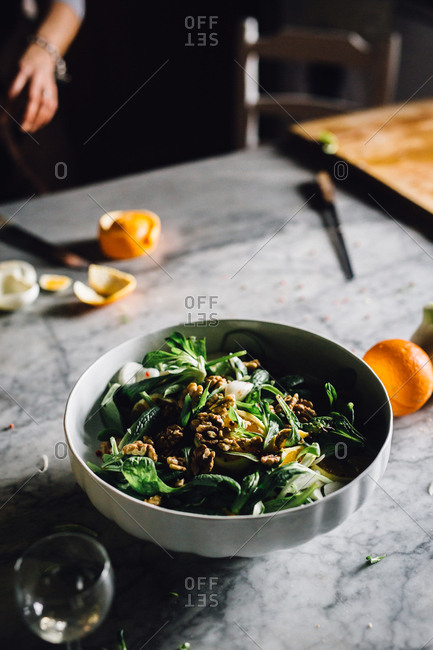 A salad with walnuts on counter