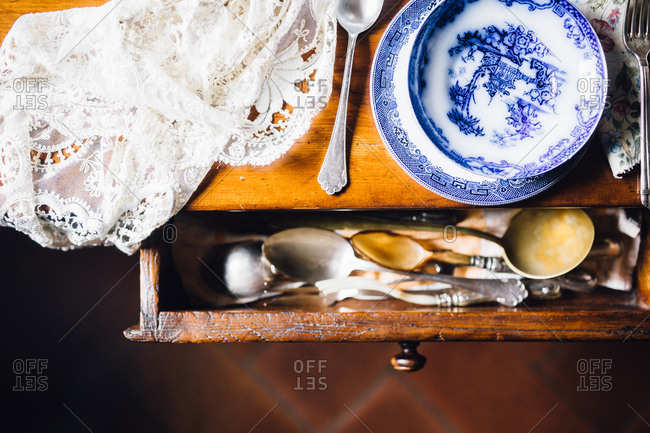 Old dishes on table with drawer
