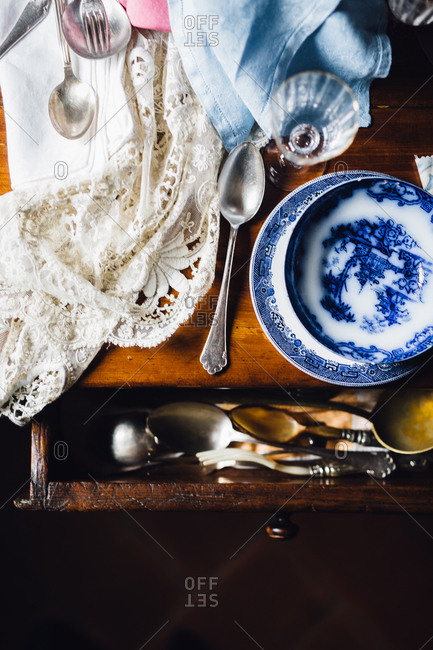 Old dishes on a table with drawer