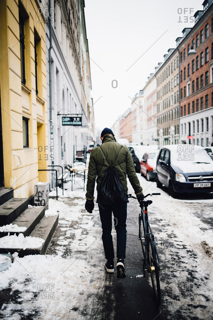 Copenhagen, Denmark - February 10, 2017: Man walking with bike in street