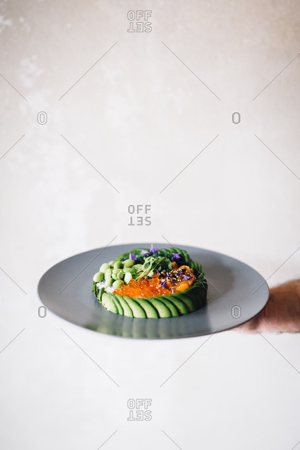 Hand holding caviar vegetable plate