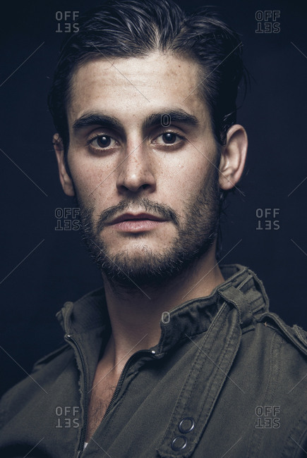 Head shot of a man  posing at camera with a cool green military jacket in Madrid, Spain