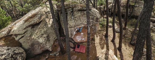 Panoramic high angle view of a woman climbing sheer boulder in Albarracin, Spain