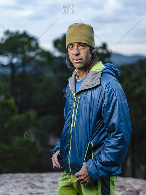 Portrait of athletic rock climber at dusk looking at camera in Albarracin, Spain