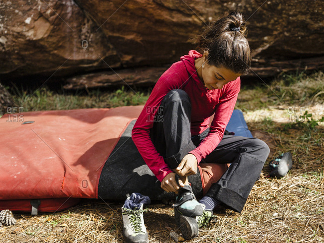Female climber buttoning her climbing shoes