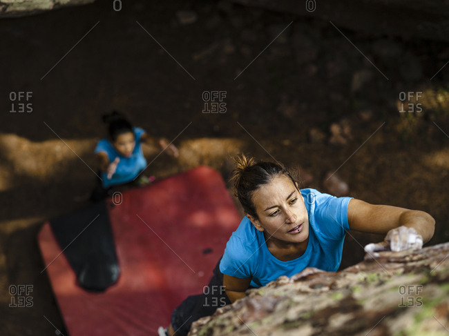 Head view of a woman climbing sheer boulder in Albarracin, Spain