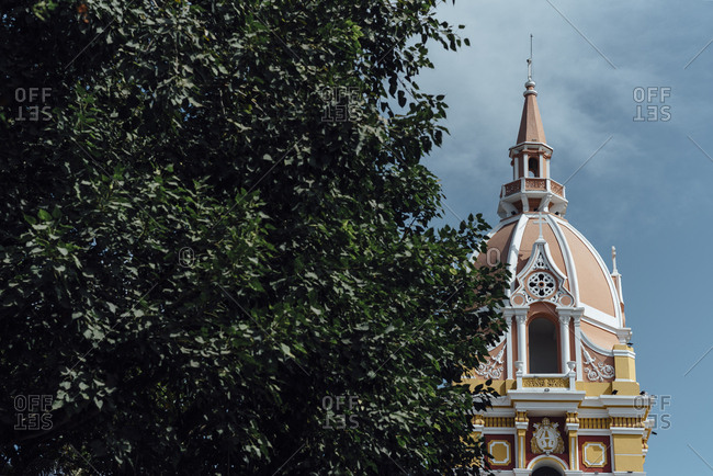View of a colonial church behind a tropical tree in the walled city of Cartagena de Indias, Colombia