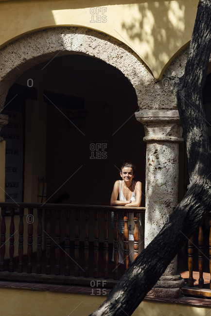 Woman leaning on the railing of a balcony of a colonial house in Cartagena de Indias, Colombia