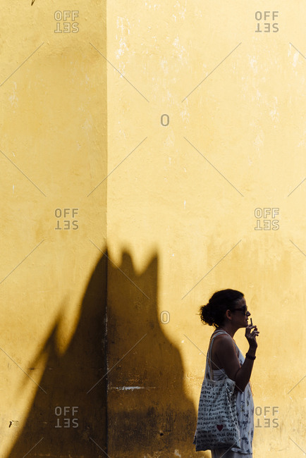 Woman smoking beside in one of the walled city streets in Cartagena de Indias, Colombia