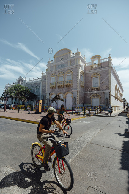 Cartagena de Indias, Colombia - March 04, 2017: Tourists riding their bikes next to the Heredia Theater in Cartagena de Indias, Colombia