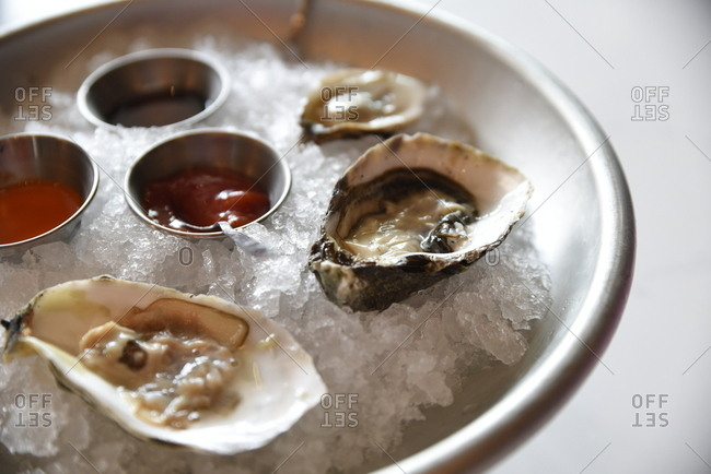 Oysters served on ice with cocktail and dipping sauces