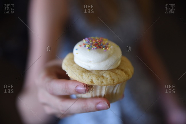 Hand of a woman holding a cupcake with rainbow sprinkles