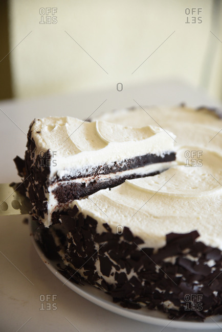 Slice of chocolate layer cake with vanilla frosting on a knife