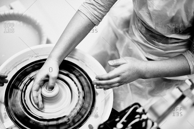 Black and white photography. Hands of girl carefully making clay jar with pottery wheel, high angle view