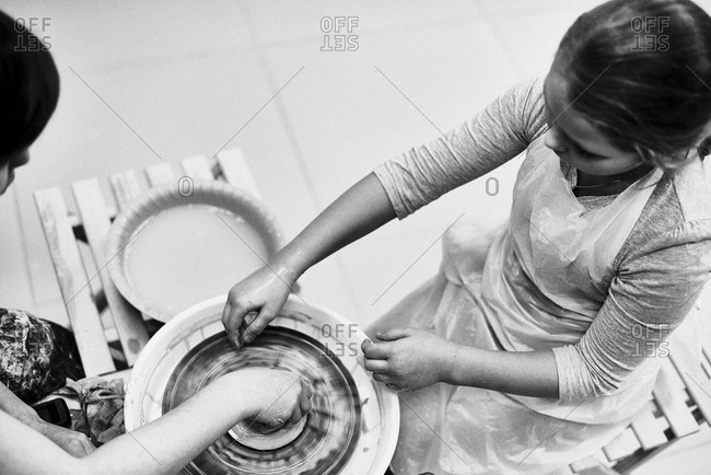Black and white photography. High angle view of woman and girl in apron molding shape of clay pot, using pottery wheel together