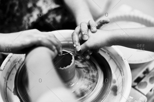 Fascinating handicraft.  Black and white close-up shot of hands using pottery wheel while shaping a large clay vase