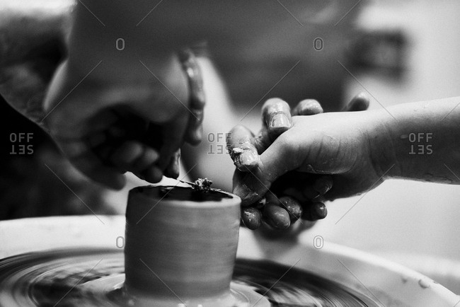 Working in pottery studio. Close-up view of hands smoothing clay pot with wire while shaping it on pottery wheel