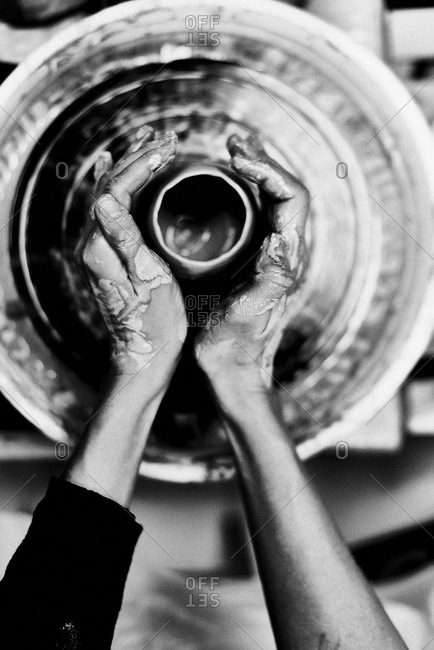 Black and white photography. Directly above view of craftsman carefully forming ceramic pot on spinning pottery wheel