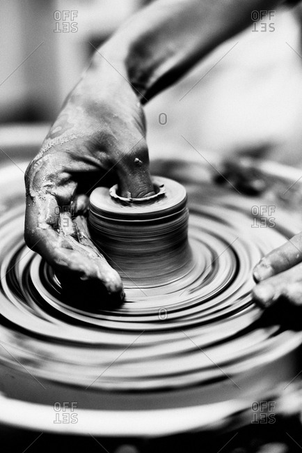 Handmade pottery. Close-up shot of hand carefully molding shape of small clay pot while it turning on pottery wheel