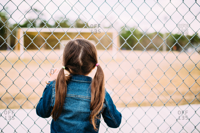 Back view of a girl looking through a chain link fence