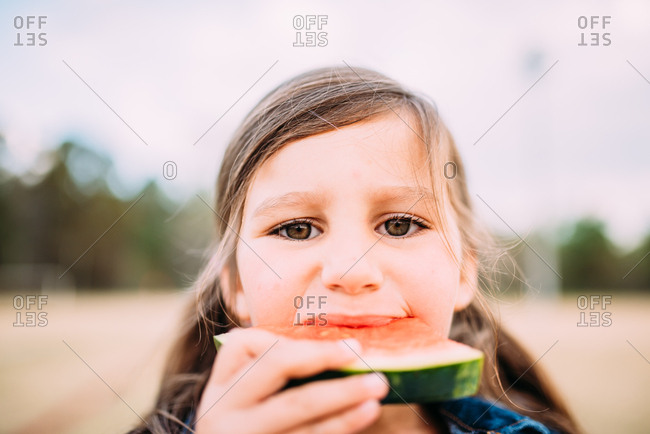 Girl eating a slice of fresh watermelon