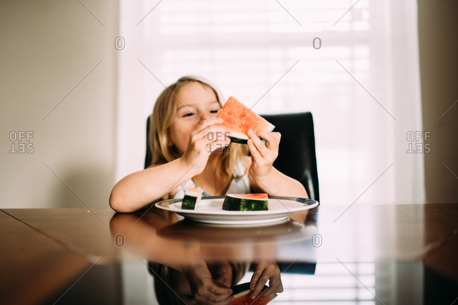Girl holding up a piece of fresh watermelon