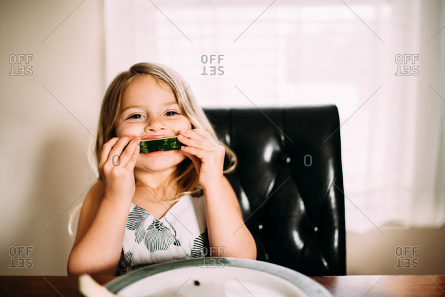 Girl eating a piece of watermelon down to the rind