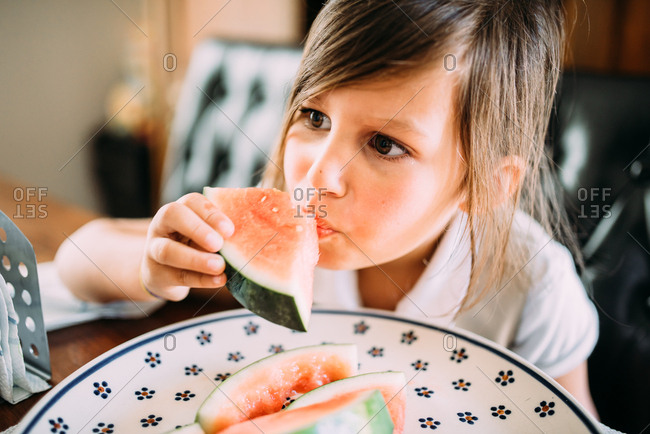 Girl eating a piece of fresh watermelon
