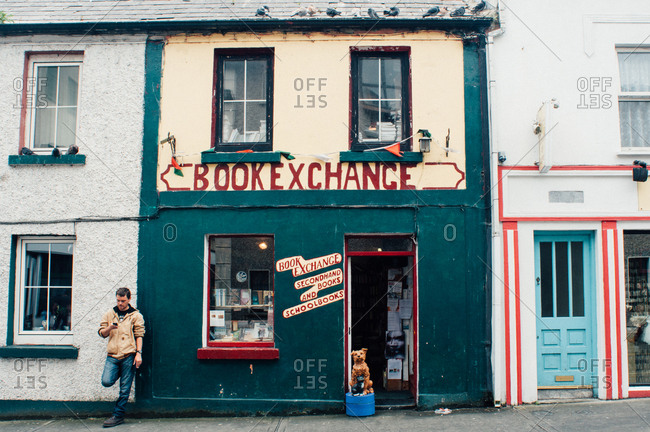 County Galway, Ireland - June 28, 2013: Man by bookstore with phone