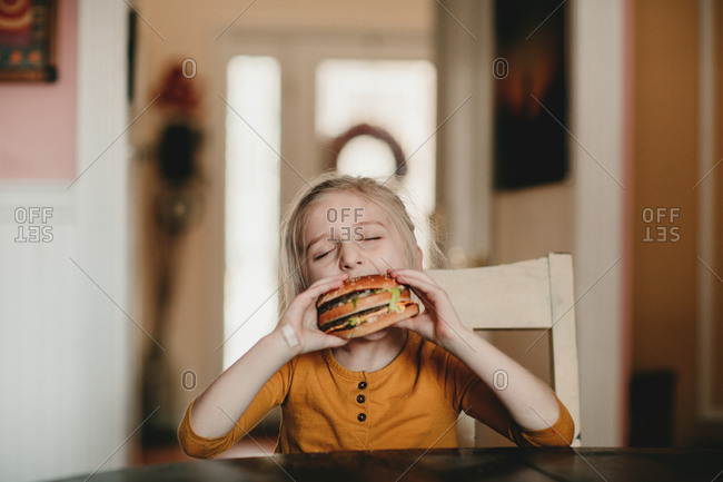 Girl taking a bite of a hamburger