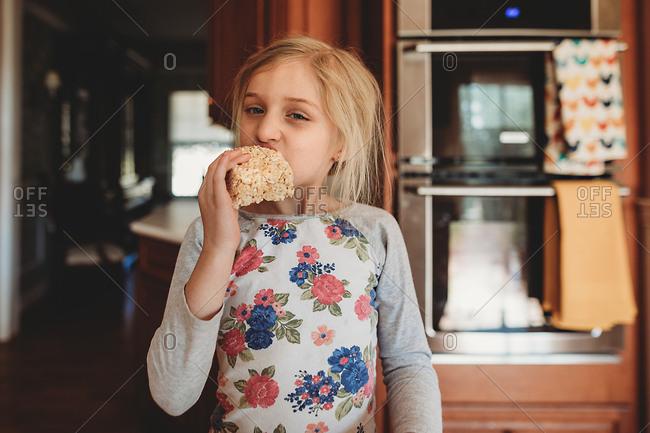 Girl taking bite of crisped rice bar