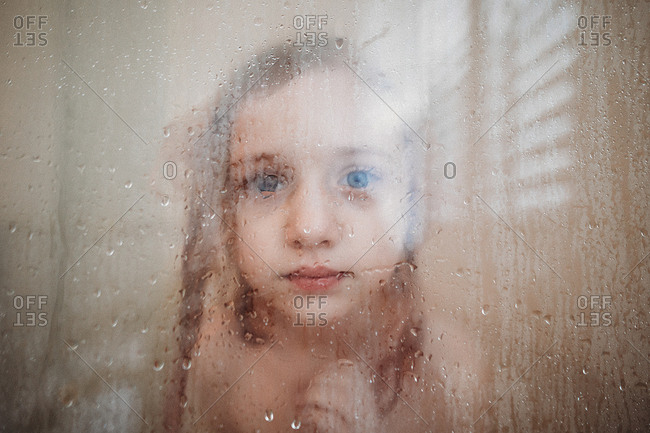 Girl in a shower looking through glass