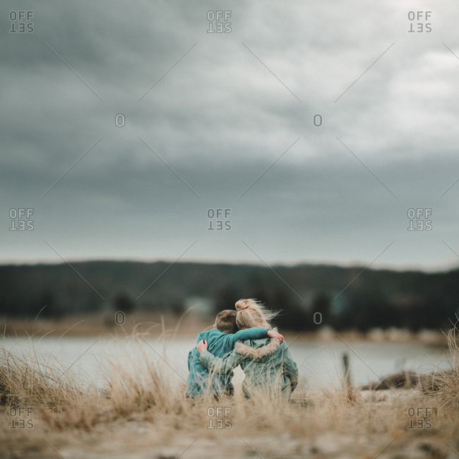 Two kids hugging on a hill