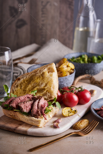 Roast beef sandwich on a board with tomatoes and French fries