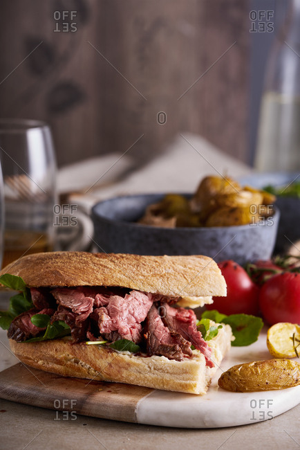 Roast beef sandwich with tomatoes and French fries on a board