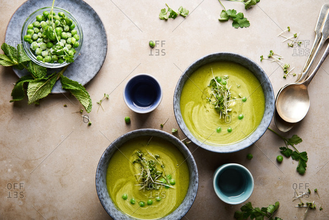 Serving bowls with fresh pea soup, cilantro and basil