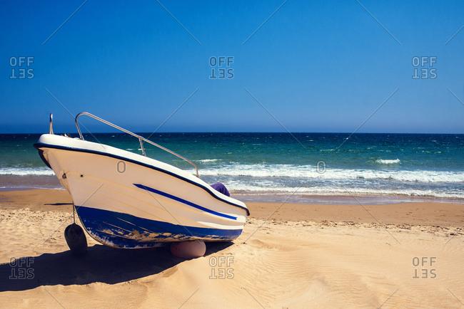 Small fishing boat on a sandy beach near the sea