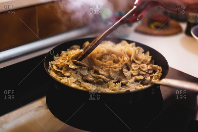 Person stirring mushrooms and bowtie pasta in a pan