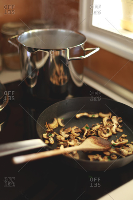 Mushrooms frying in a pan on a stove