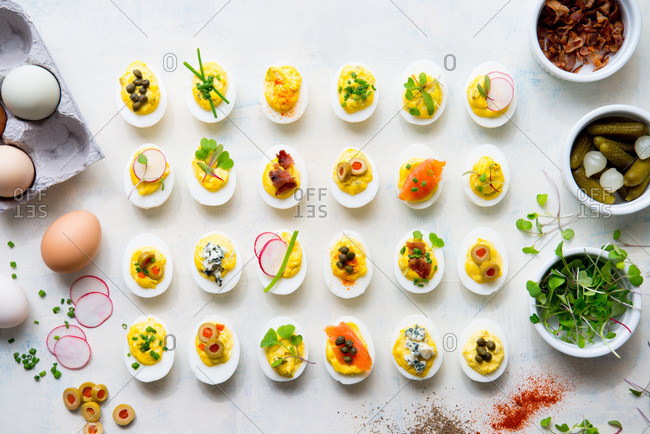 Deviled eggs with a variety of toppings arranged between ingredients