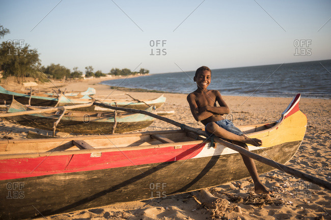 Ifaty, Toliara, Madagascar - June 17, 2016: Portrait of a child on a dugout fishing canoe on Ifaty Beach