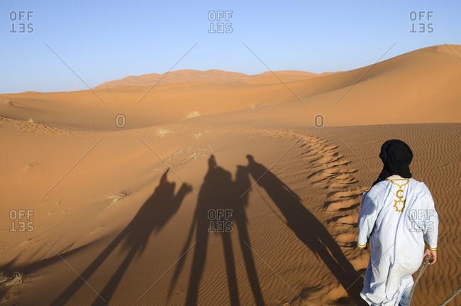 A berber man guiding tourists through the desert