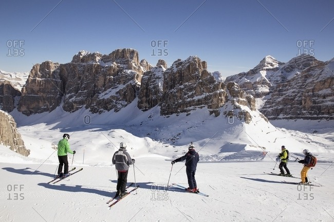 Veneto, Italy - June 23, 2016: Group of skiers on the slopes below the Fanis group and Tofana di Rozes