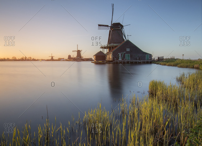 Windmills at sunset along the banks of the river Zaan in the little village of Zaanse Schans