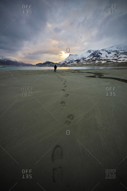 A person in front of the bank of the Mont Cenis lake leaves footprints on his path on the sandy bottom