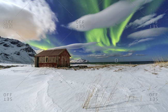 Northern Lights over an abandoned log cabin surrounded by snow and ice