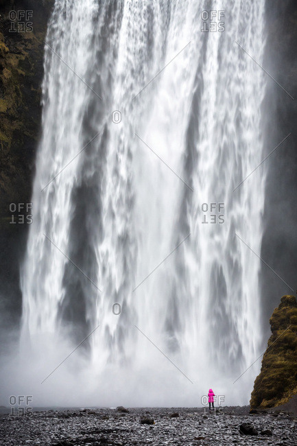 Woman staring at Skogafoss waterfall