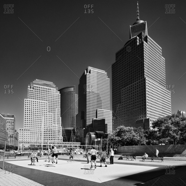New York City, USA - August 8, 2016: View of the Tower and WTC buidings from the North Cove Marina with people playing volley during lunchtime